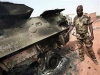 "Nigerian wheeled armoured personnel carrier Piranha I Grizzly picture. An African Union Mission in the Sudan (AMIS) peacekeeper from Nigeria points to the blast point of a rocket-propelled grenade on a destroyed armoured personnel carrier at Haskanita military group site (MGS), October 1, 2007. Twenty AU soldiers were killed or injured and nine missing after a ""deliberate and sustained"" assault on the Haskanita base in Darfur on Saturday night by armed men in 30 vehicles, who looted and destroyed the base, the African Union said."