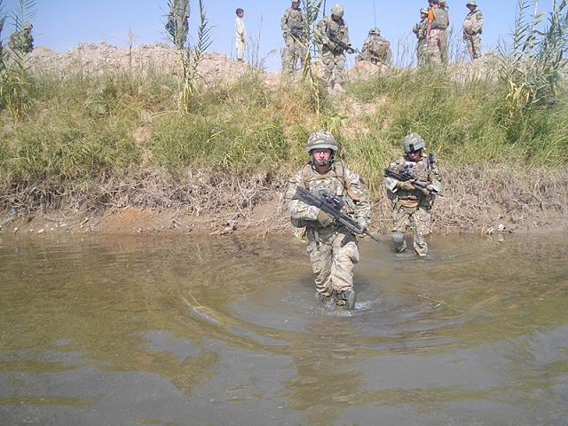British army soldiers from C Company, 1st Battalion The Princess of Wales's Royal Regiment, wade into a river during Operation TORA GHAR